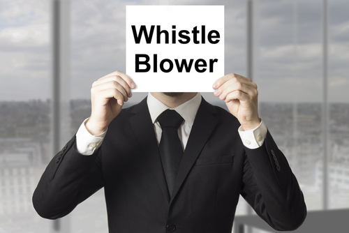 business man holding whistle blower sign over face.